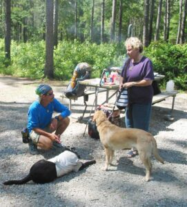 """I've got more miles on me than a lot of used cars,"" says long-distance hiker, Trevor Thomas, in remarks to Compass reporter Penny Zibula. Guide dogs for Thomas and Zibula are also shown in the photo."