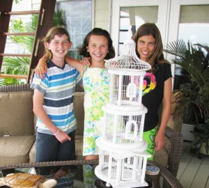 Vivian Reed, left, is seen here with friends Savannah Pittman and Caroline James, next to a cage where an injured purple martin received tender, loving care.