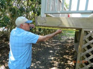 Bill Minchin, president of the Oriental West homeowners association, uses a tape measure to demonstrate a 35-inch encroachment that must be sawed off, after a unanimous decision of the town board Tuesday night.