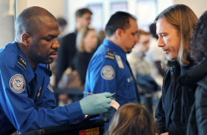 A screener with the Transportation Security Agency checks the ID of a passenger at LaGuardia International Airport in New York City.