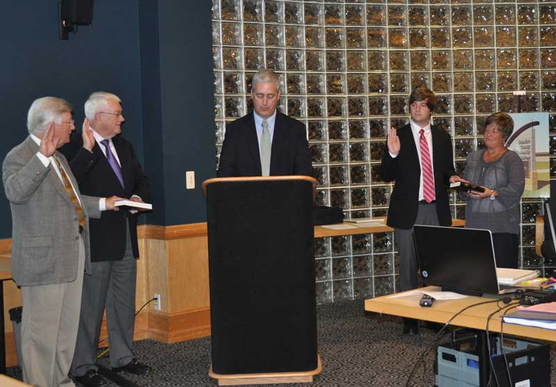 Clerk of Court Marty Paramore, center, gives the oath office to three new members of the Beaufort County Community College Board of Trustees. They are, left to right, Bill Wall, Jim Chesnutt and Jackson Lancaster. At right, Lancaster's mother, Louann, participates in the ceremony.