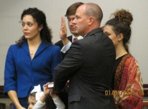 Among family members, Andy Womble takes the Oath of Office.
