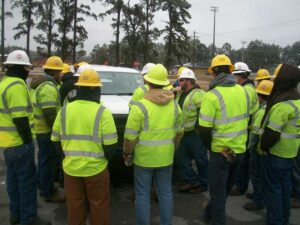 Just before dark, workers gather around the pickup truck of a supervisor to receive their marching orders.