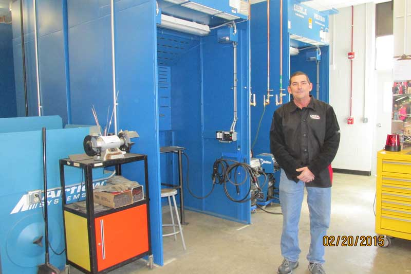 Instructor Mike Lopes stands beside one of the school's high-tech welding booths.