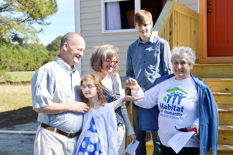 Ari Sylvester receives the key to her family's new home from Rosemary Warner, president of the Pamlico County Chapter of Habitat for Humanity. From left, are John Sylvester;  daughter, Victoria; Ari Sylvester; son, Alden; and Rosemary Warner, President of Pamlico County Habitat For Humanity.
