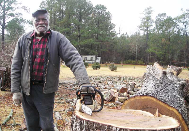 The deceased man, Joe Thomas Jones, is seen in this file photo from January 2011, cutting firewood outside his home on Janeiro Road, where the killings occurred Saturday.  (Exclusive Photo)