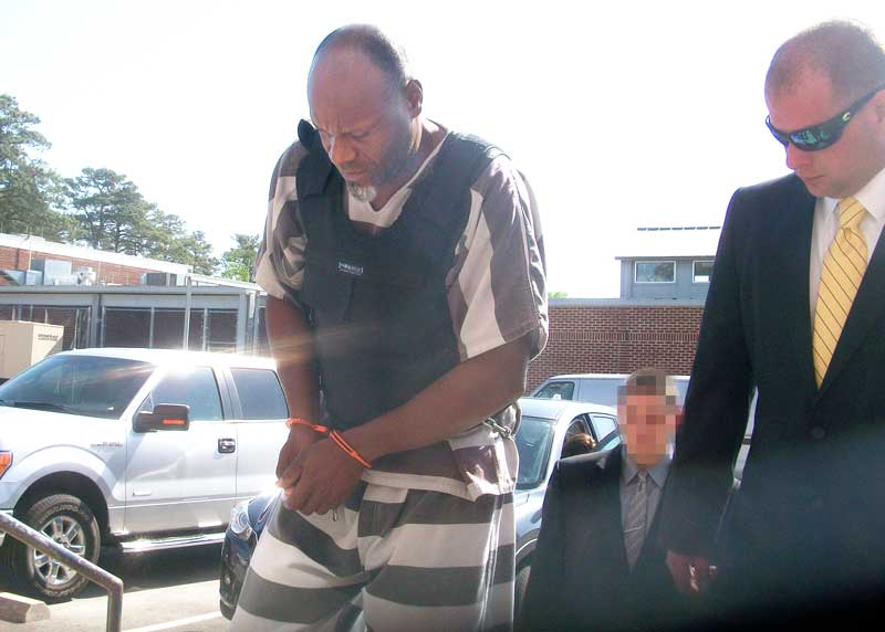 The accused double-murderer entered the courthouse flanked by several Pamlico County deputies.