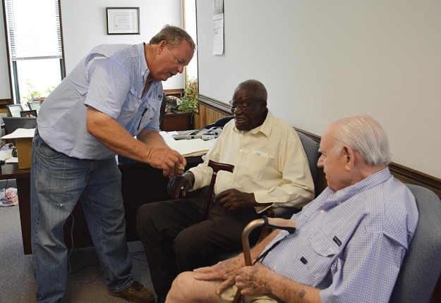 Reuben Peed, 87, accepts a gold watch from Joe Hooker, president of CMF, while John Hooker Sr., CEO of CMF looks on.