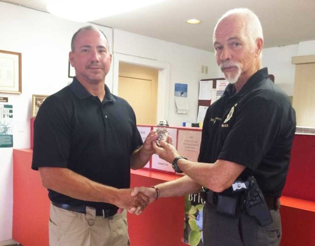 At left, Ken Heath, a Pamlico County Commissioner, recently completed Basic Law Enforcement Training, and accepts his badge Friday afternoon from instructor Rick Barney.