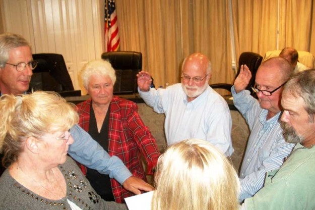 In foreground, Oriental Town Manager Diane Miller holds a Bible for five town commissioners as Assistant Clerk of Court Sandy Clark administers the Oath of Office. From left, clockwise, are Commissioners David White, Barb Venturi, Charlie Overcash, Allen Price, and Sandy Winfrey.