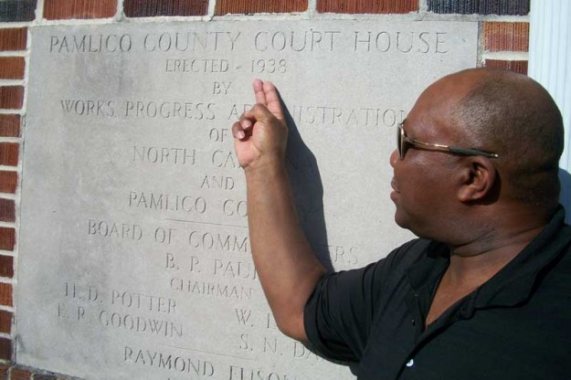Beside the engraved cornerstone of the Bayboro Courthouse, County Commissioner Carl Ollison points to the year of construction – 1938.