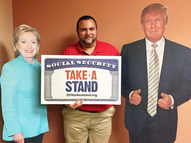 Leo Scarpati, AARP Associate State Director, poses with cardboard cutouts of Hillary Clinton and Donald Trump in preparation for the 'Take A Stand' marketing effort during the Cherry Point Air Show this weekend.